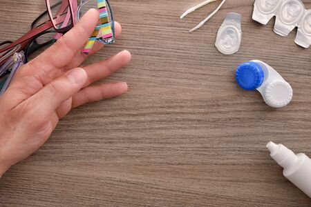 A man's hand rejecting a lot of glasses in favor of contact lenses on wood table. Horizontal composition. Top view.