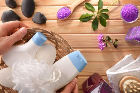 Hands showing bath hygiene products and other massage products on wooden table. Top view. Horizontal composition. Stock Photo