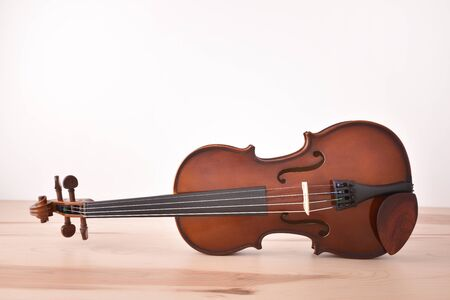 Violin on wooden table and white background. Horizontal composition. Front view