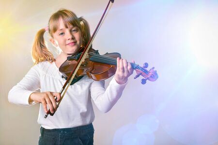 Girl performing on stage with violin. Horizontal composition. Front view. Reklamní fotografie