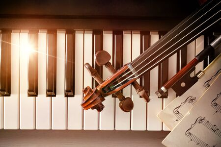 Violin pegbox bow and sheet music on piano keys. Concept of interpretation of piano music and string instruments. Top view. Horizontal composition.