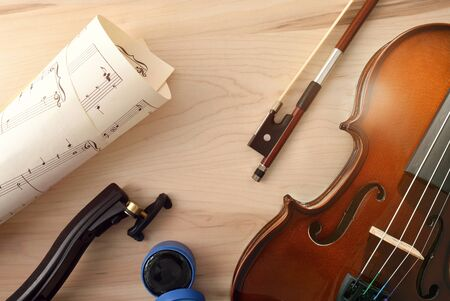 Violin and equipment on wooden table. Top view. Horizontal composition.