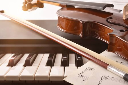 Violin bow and sheet music on piano keys. Concept of interpretation of piano music and string instruments. Front view. Horizontal composition.