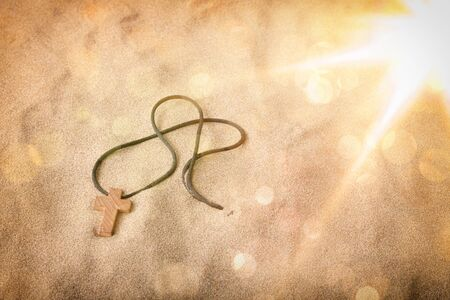 Half-buried crucifix in sand with glitter and bokeh. Horizontal composition