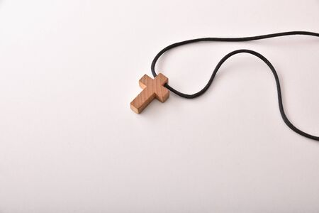 Wooden crucifix with black cord on white table. Horizontal composition. Top view.