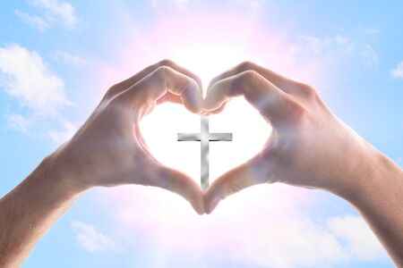 Hands of a man forming a heart in heaven with spikes surrounding a cross. Horizontal composition
