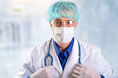 Doctor in his forties with face protection such as a mask, glasses and cap, dressed in a white uniform with a stethoscope hanging from his neck in hospital corridor Imagens - 143138153