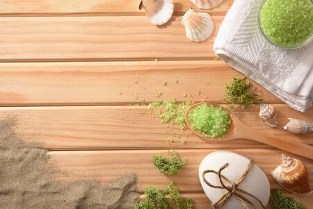 Marine salts and thalassotherapy products for body treatment on wooden slats table decorated with seaweed shells and sand. Top view. Horizontal composition.