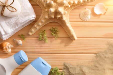 Thalassotherapy products for body treatment on wooden slats table decorated with starfish seaweed shells and sand. Top view. Horizontal composition.