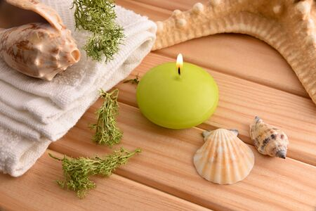 Thalassotherapy treatment concept with burning candle and sea shells on wooden table. Elevated view. Horizontal composition.