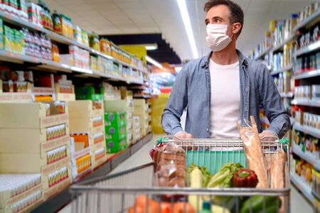 Man with mask protection and gloves pushing a cart full of food in a supermarket