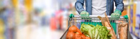 Detail of a protected man with gloves pushing a cart full of basic food in supermarket