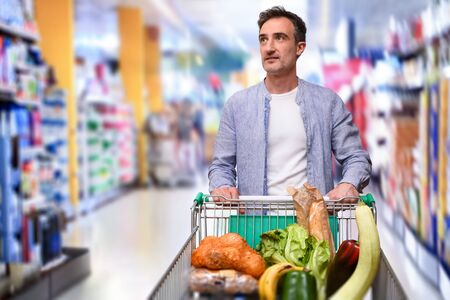 Casual man buying and pushing a shopping cart full of food in a supermarket aisle coming from the front Foto de archivo
