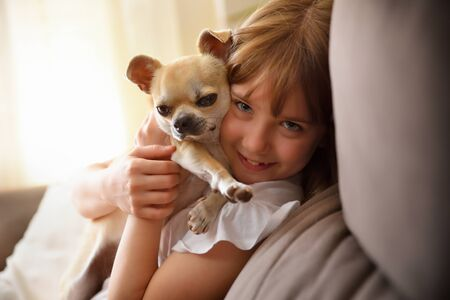 Smiling girl caught face to face with her dog on a sofa at home Imagens