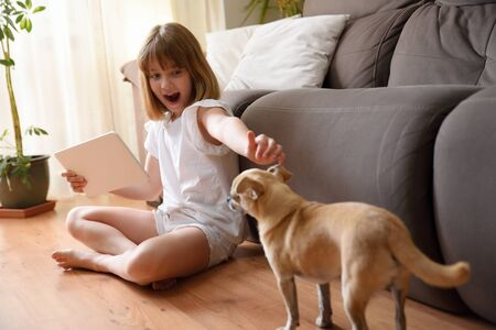 Little girl entertaining at home with a tablet in her hand and playing with her dog