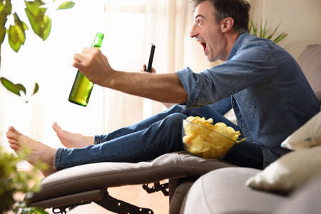 Man watching sports on television sitting comfortably on a sofa having a snack with beer and a remote control in his hands. Imagens