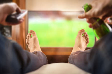 man sitting on a sofa watching match on TV with remote control and beer at home Imagens