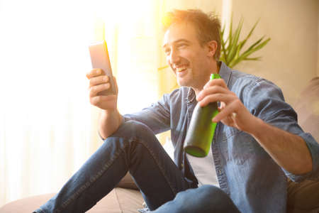 Man smiling drinking a beer from a bottle and having snack sitting on the sofa in the living room at home