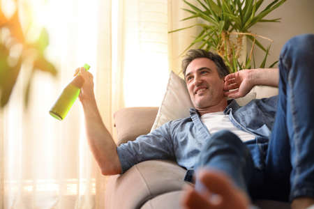 Relaxed smiling man drinking a beer lying on a sofa in the living room at home. Imagens
