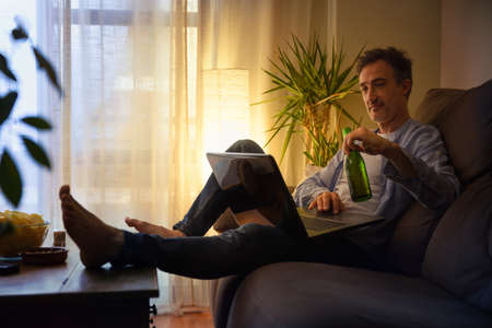 Relaxed man entertaining with a laptop at home having a beer sitting on a sofa Imagens