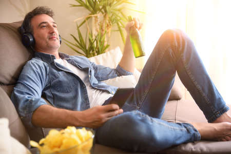 Relaxed man listening to music with headphones from a mobile phone with a beer in his hand sitting on a sofa at home comfortably Imagens