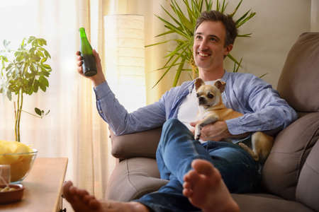 Resting smiling man having a snack sitting on a sofa at home with his dog in the arms Imagens