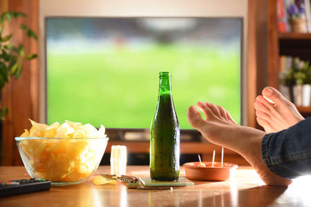 Man at home watching game on television with feet on side table and snack.