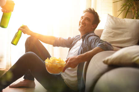 happy man sitting on the floor leaning on a sofa having a snack with beer at home with friends Imagens