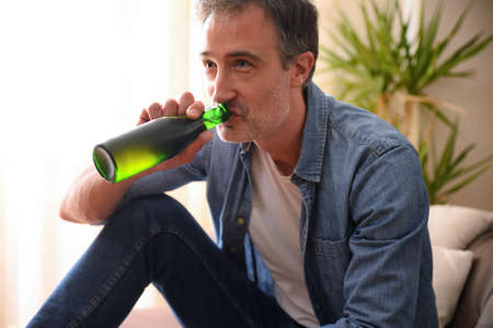 Man drinking from a bottle of beer sitting on the sofa in the living room at home