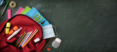 Backpack full of school supplies on green blackboard with protection mask and hydroalcoholic gel with blank space to write top view. Imagens