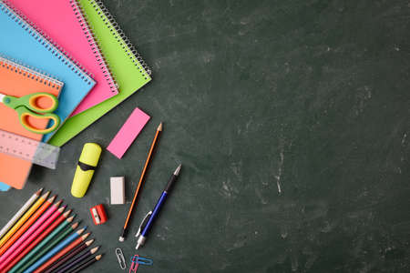 School educational supplies such as notebooks, colored pencils and others on green blackboard. Top view.