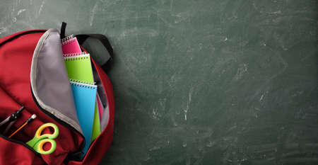 Backpack full of school supplies on green blackboard with blank space for writing top view Imagens