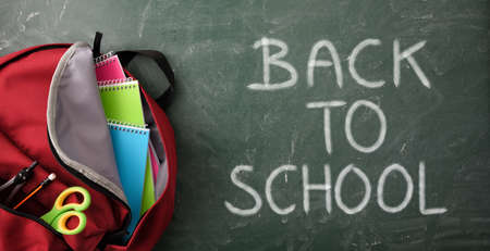 Detail of backpack full of school supplies on green blackboard with back to school message. Top view Imagens
