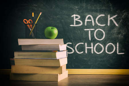 Stack of books with pencil and apple on class table with green chalkboard in background with back to school message. Concept of studying.