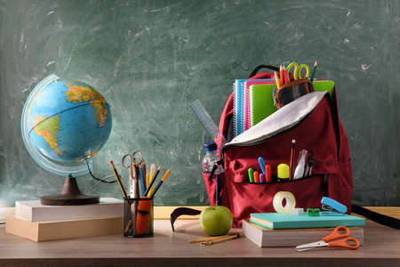 Class with backpack with school supplies on wooden desk and green chalkboard background Imagens