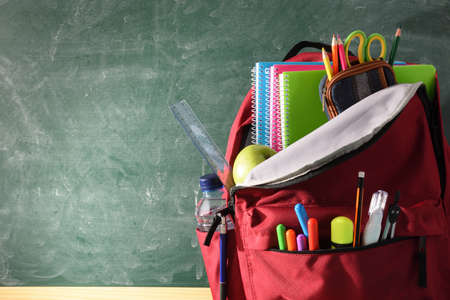 Backpack full of school supplies on wood table and green blackboard with blank space for writing front view Imagens