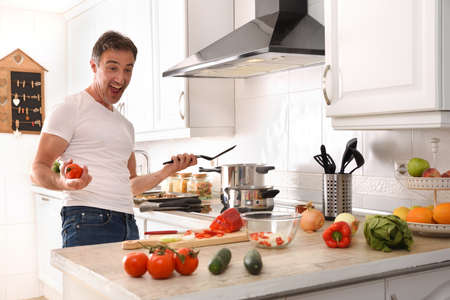Happy and expressive man happily cooking vegetables at home in a home kitchen