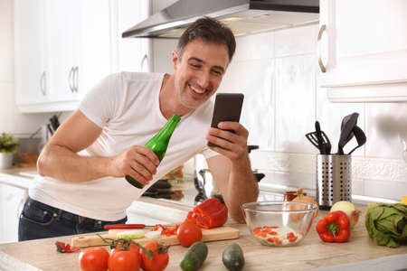 Happy man in the kitchen looking at a cell phone and having a beer while cooking leaning on the bench with vegetables Imagens