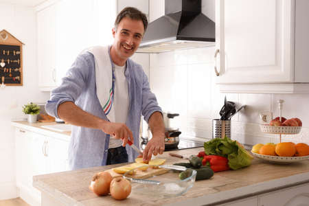 Smiling man cutting potatoes for baking on kitchen bench with vegetables.