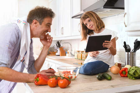 Girl sitting on a kitchen bench showing her father a digital recipe from a tablet to prepare a dish