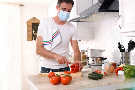 Man preparing vegetables to make a plate of food confined by covid-19 at home with mask Imagens
