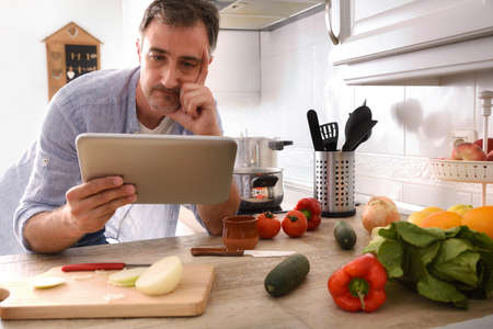Doubtful man cooking at home looking at recipe on a tablet leaning on the kitchen bench with his hand on his face Imagens