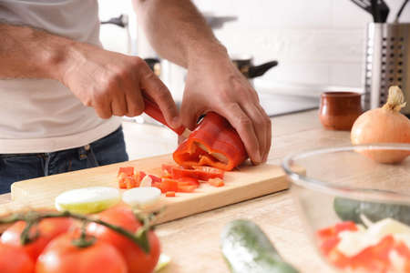 Hands of a casual man cutting a bell pepper on cutting board on the kitchen bench with vegetables around Imagens