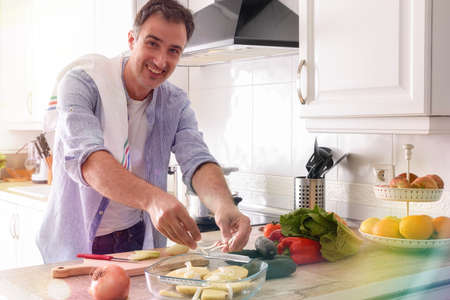 Smiling man preparing potatoes for baking on kitchen bench with vegetables.