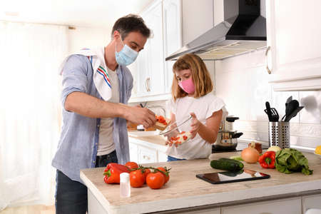 Happy father and daughter preparing vegetables to make a plate of food confined by covid-19 at home with masks Imagens