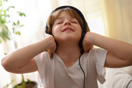 Little girl listening passionately to music holding earphones in a warm room at home