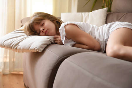 Little girl sleeping on a sofa at home Imagens