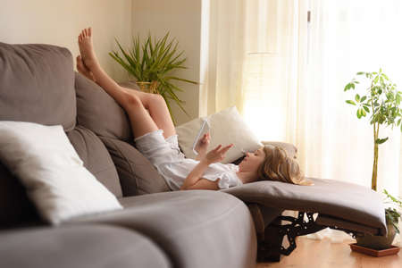 Little girl lying on the sofa in her living room waving by video conference on a tablet