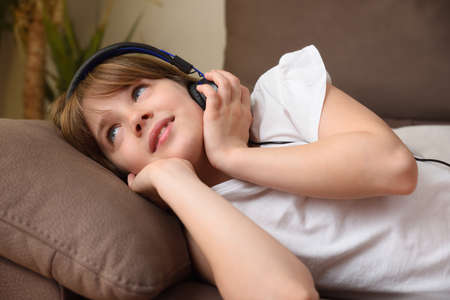 Girl with helmets listening to music lying on the sofa at home in a quiet and warm environment
