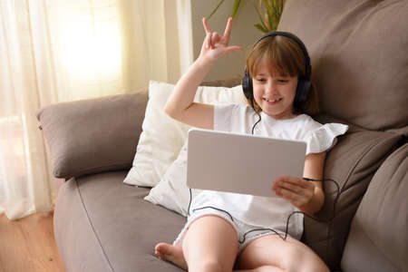 Happy little girl lying on the sofa in her living room waving funny by video conference on a tablet. Imagens